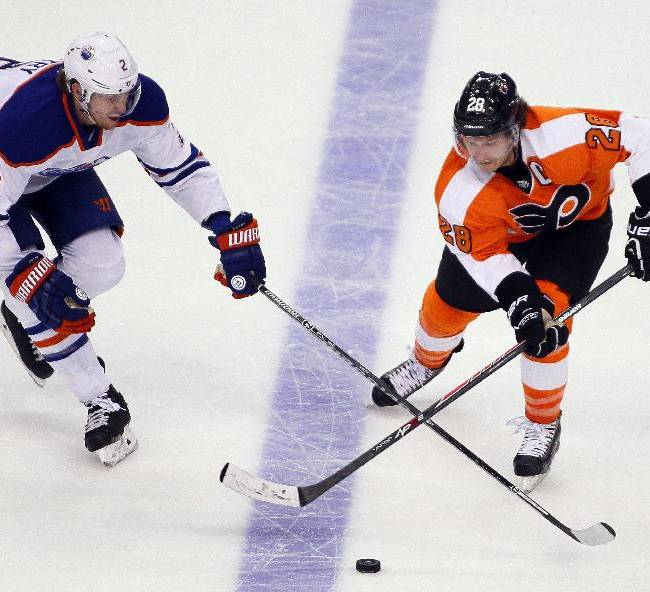 Edmonton Oilers' Jeff Petry, left, and Philadelphia Flyers' Claude Giroux chase the puck during the third period of an NHL hockey game, Saturday, Nov. 9, 2013, in Philadelphia. The Flyers won 4-2