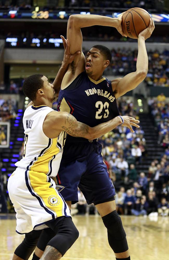 New Orleans Pelicans forward Anthony Davis (23) keeps the basketball away from Indiana Pacers guard George Hill during the second half of an NBA basketball game in Indianapolis, Saturday, Jan. 4, 2014. Indiana won 99-82