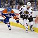 Chicago Blackhawks' Patrick Kane (88) and Edmonton Oilers' Justin Schultz (19) reach for the puck during the first period of an NHL hockey game Friday, Jan. 9, 2015, in Edmonton, Alberta The Associated Press