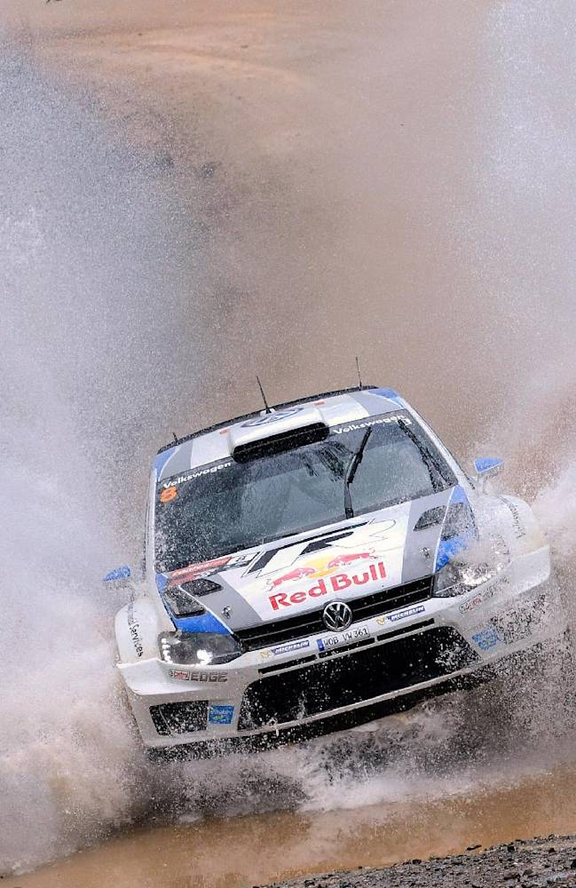 In this photo provided by Rally Australia, Sebastien Ogier of France and his co-driver Julien Ingrassi race through water during the Rally Australia at Coffs Harbour, Sunday, Sept. 15, 2013. Ogier won the rally in dominant fashion but will have to wait to clinch the 2013 World Rally Championship title