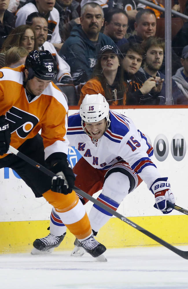 Philadelphia Flyers' Nicklas Grossmann, left, tries to keep the puck away from New York Rangers' Derek Dorsett during the first period of an NHL hockey game, Saturday, March 1, 2014, in Philadelphia