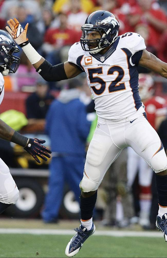 In this Dec. 1, 2013 file photo, Denver Broncos middle linebacker Wesley Woodyard (52) celebrates with defensive end Robert Ayers (91) after intercepting a pass during the first half of an NFL football game against the Kansas City Chiefs in Kansas City, Mo. The Tennessee Titans have agreed to terms on a multiyear deal with free-agent linebacker Wesley Woodyard, who spent the last six years with the Denver Broncos