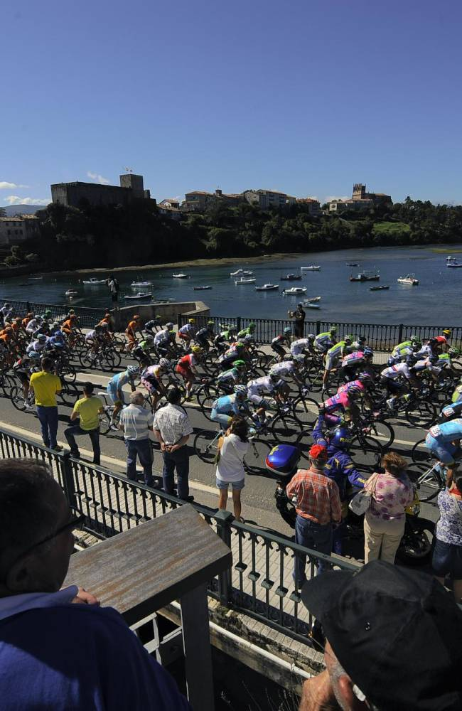Spectators watch as the peloton cross a bridge spanning the Cantabrico Sea as they begin the 19th stage of the Vuelta cycling race, a 181-kilometer (112,5-mile) leg between San Vicente de La Barquera and Oviedo, in San Vicente de La Barquera, northern Spain, Friday, Sept. 13, 2013