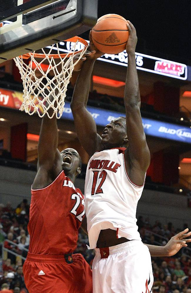 Louisville's Mangok Mathiang, right, is fouled by Akoy Agau during an NCAA college basketball scrimmage Saturday, Oct. 19, 2013, in Louisville, Ky