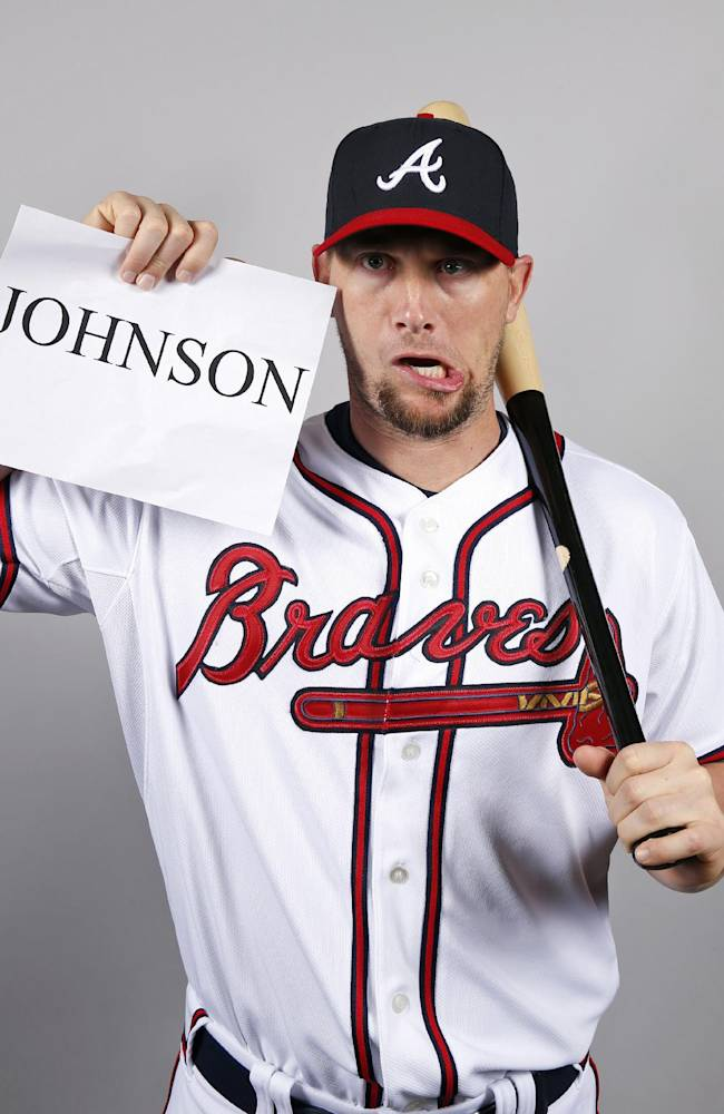 Atlanta Braves third baseman Chris Johnson makes a funny face while holding up his name placard for photo day before a spring training baseball workout, Monday, Feb. 24, 2014, in Kissimmiee, Fla