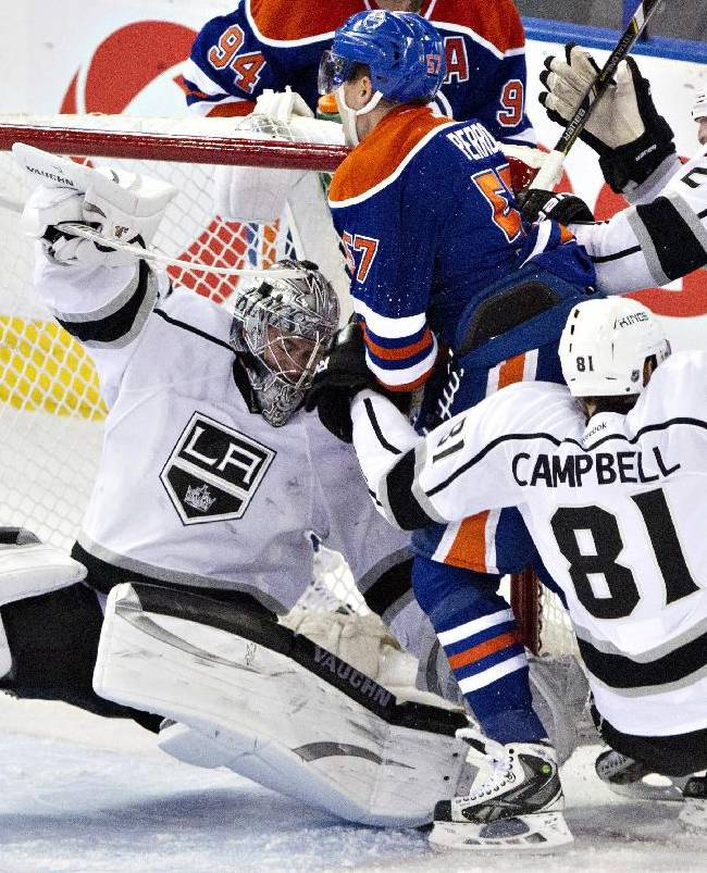 Los Angeles Kings goalie Martin Jones is knocked over as Edmonton Oilers' David Perron (57) and Oilers' Andrew Campbell (81) and Matt Greene (2) crash the net during the third period of an NHL hockey game Thursday, April 10, 2014, in Edmonton, Alberta. The Kings won 3-0