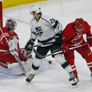 Los Angeles Kings' Jarret Stoll (28) looks back at the puck bouncing off Carolina Hurricanes goalie Cam Ward (30) as he is defended by Hurricanes' Justin Faulk (27) during the third period of an NHL hockey game in Raleigh, N.C., Sunday, Nov. 2, 2014. Hurr