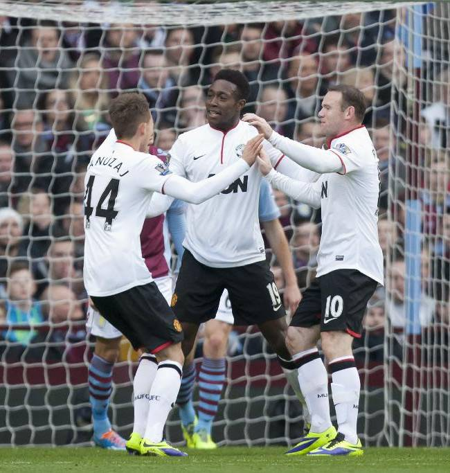 Manchester United's Danny Welbeck, centre, celebrates with teammates Wayne Rooney, right, and Adnan Januzaj after scoring his first goal against Aston Villa during their English Premier League soccer match at Villa Park Stadium, Birmingham, England, Sunday Dec. 15, 2013
