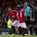 Manchester United's Jesse Lingard, centre left, goes on the pitch after teammate Juan Mata is substituted, during a pre season friendly soccer match against Valencia at Old Trafford Stadium, Manchester, England, Tuesday Aug. 12, 2014