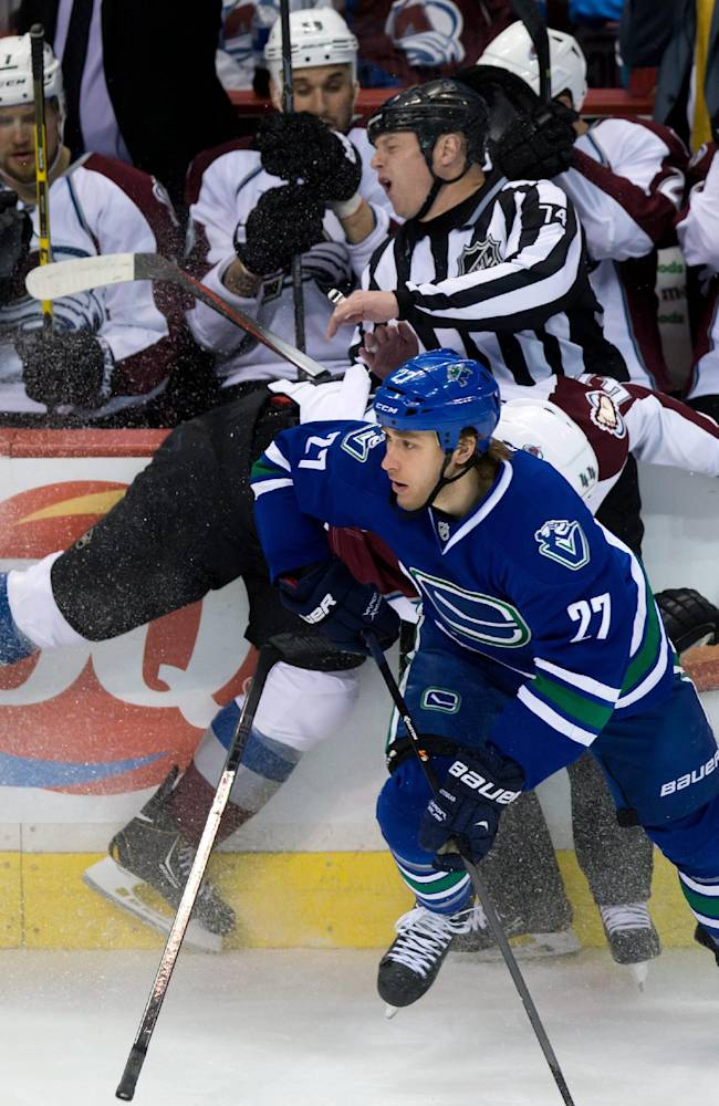 Colorado Avalanche's Ryan Wilson, middle, collides with linesman Lonnie Cameron while trying to check Vancouver Canucks' Shawn Matthias during the third period of an NHL hockey game Thursday, April 10, 2014, in Vancouver, British Columbia
