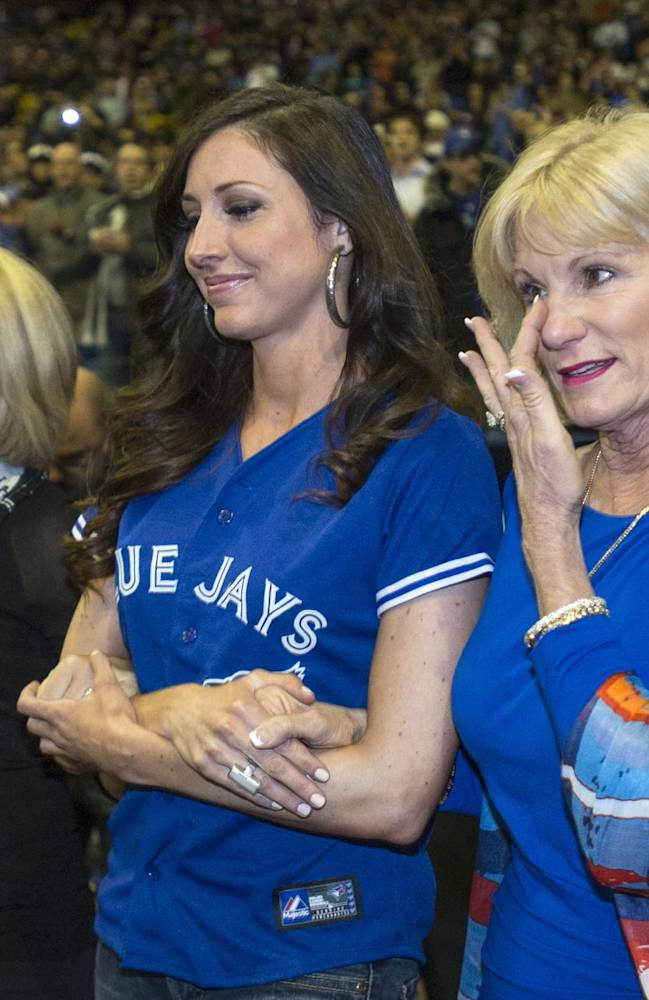 Sandy Carter, wife of former Montreal Expos catcher Gary Carter, wipes her eye as she and her daughter Kimmy, left, are introduced during a ceremony prior to a pre-season exhibition game between the Toronto Blue Jays and the New York Mets Friday, March 28, 2014 in Montreal