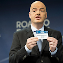 UEFA General Secretary Gianni Infantino, shows a ticket with British soccer team Manchester City FC during the draw of the round of 16 of the UEFA Champions League 2014/15 soccer matches in Nyon, Switzerland, Monday, Dec. 15, 2014