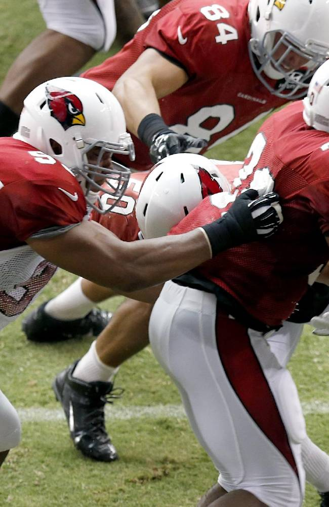 Arizona Cardinals' Calais Campbell, left, tackles Stephan Taylor (30) during NFL football training camp practice on Wednesday, July 30, 2014, in Glendale, Ariz