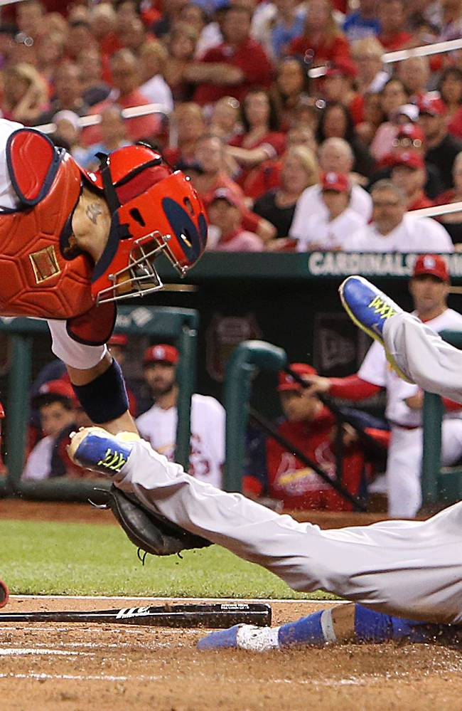 In this May 12, 2014 photo, Chicago Cubs' Emilio Bonifacio scores past St. Louis Cardinals catcher Yadier Molina on a fielder's choice by Anthony Rizzo in the fourth inning of a baseball game at Busch Stadium in St. Louis.  Bonifacio was originally called out by home plate umpire Paul Schreiber, right,  but the call was overturned upon review. The Cubs beat the Cardinals 17-5