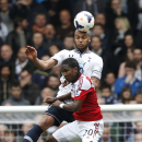 Tottenham Hotspur's Younes Kaboul, top, competes with Fulham's Hugo Rodallega during their English Premier League soccer match at White Hart Lane, London, Saturday, April 19, 2014