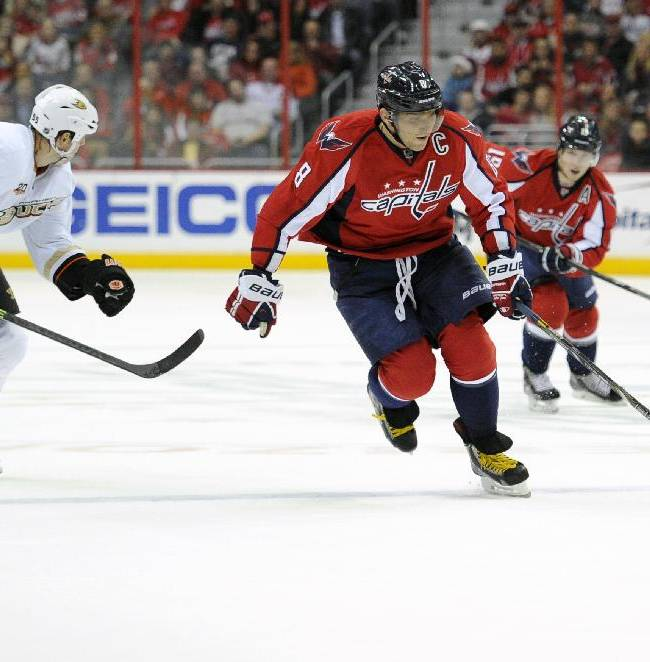 Washington Capitals right wing Alex Ovechkin (8), of Russia, races down the ice with the puck against Anaheim Ducks defenseman Bryan Allen (55) during the first period of an NHL hockey game, Monday, Dec. 23, 2013, in Washington
