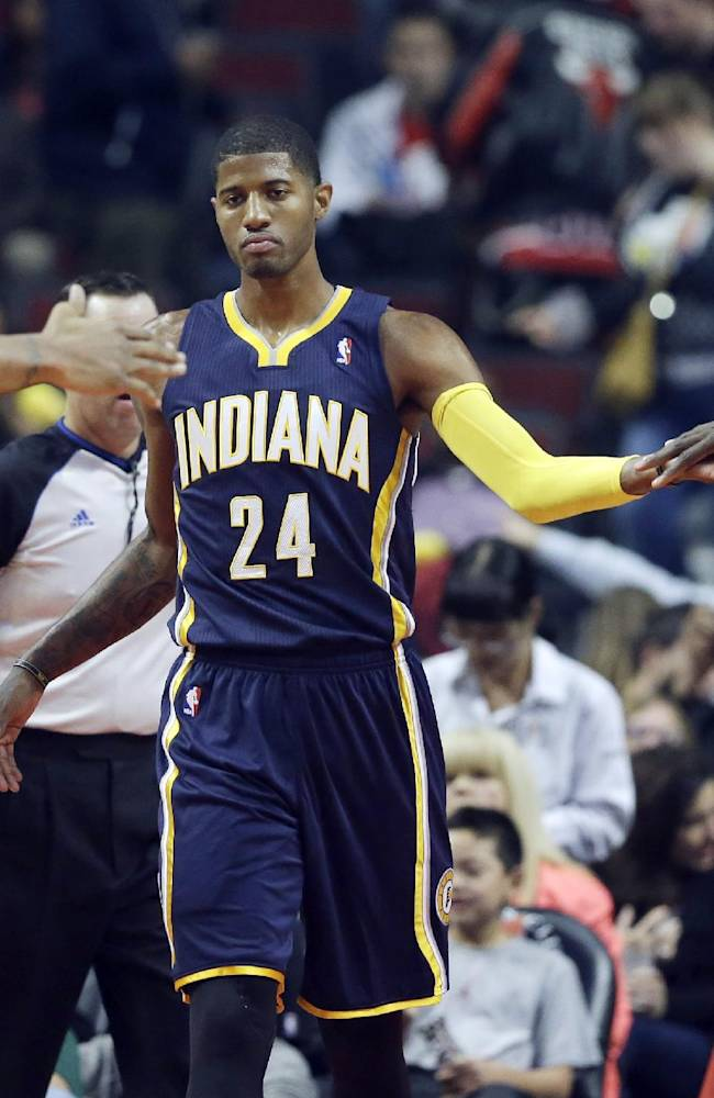 Indiana Pacers guard Paul George (24) celebrates with center Roy Hibbert (55), right, and forward David West (21) after Chicago Bulls center Nazr Mohammed fouled during the first half of an NBA preseason basketball game in Chicago on Friday, Oct. 18, 2013
