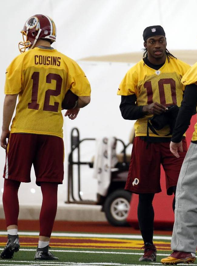 Washington Redskins quarterbacks Kirk Cousins, left, Robert Griffin III, and Rex Grossman talk during their NFL football practice Wednesday, Dec. 11, 2013, in Ashburn, Va. Cousins will start for the Redskins on Sunday, and Griffin III will be the No. 3 quarterback behind Grossman