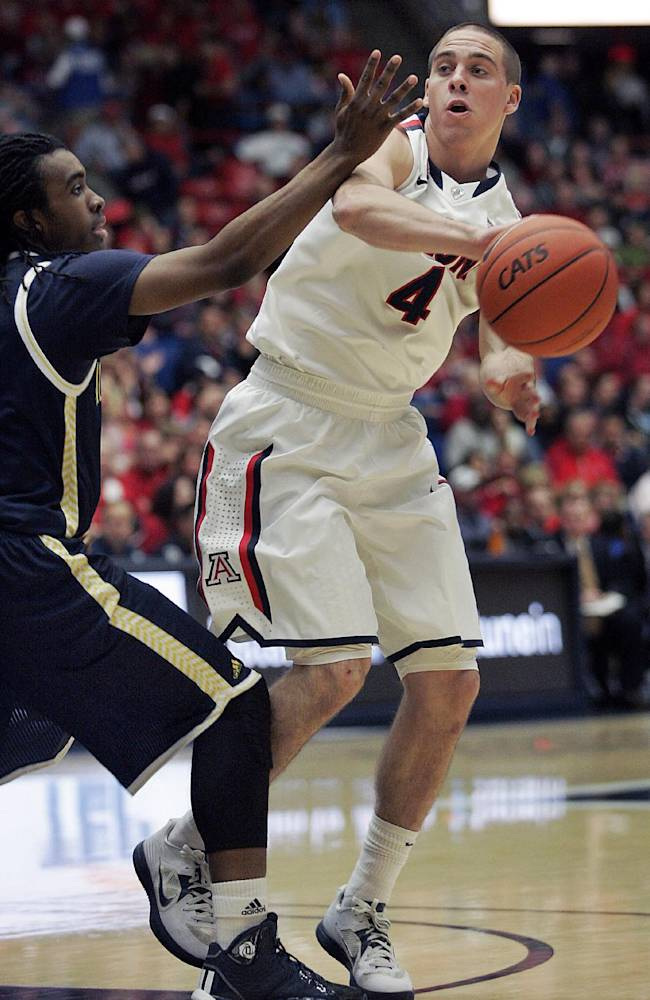 Arizona's T.J. McConnell (4) passes against the defense of Northern Arizona's Aaseem Dixon, left, during the first half of an NCAA college basketball game Monday, Dec. 23, 2013, in Tucson, Ariz