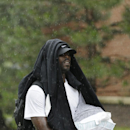 In the rain, New York Jets' quarterback Michael Vick arrives for NFL football training camp on Wednesday, July 23, 2014, in Cortland, N.Y The Associated Press