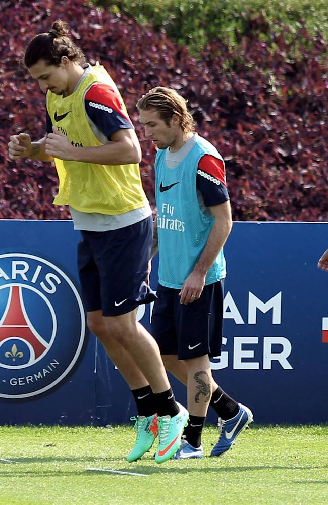 Paris Saint-Germain's players warm up during a training session at the Aspire Academy of Sports Excellence in Doha, Qatar, Tuesday, Dec. 31, 2013