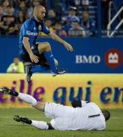 Montreal Impact's Marco Di Vaio leaps over Houston Dynamo goalkeeper Tally Hall during the second half of an MLS soccer game in Montreal, Saturday, Aug. 24, 2013. (AP Photo/The Canadian Press, Graham Hughes)