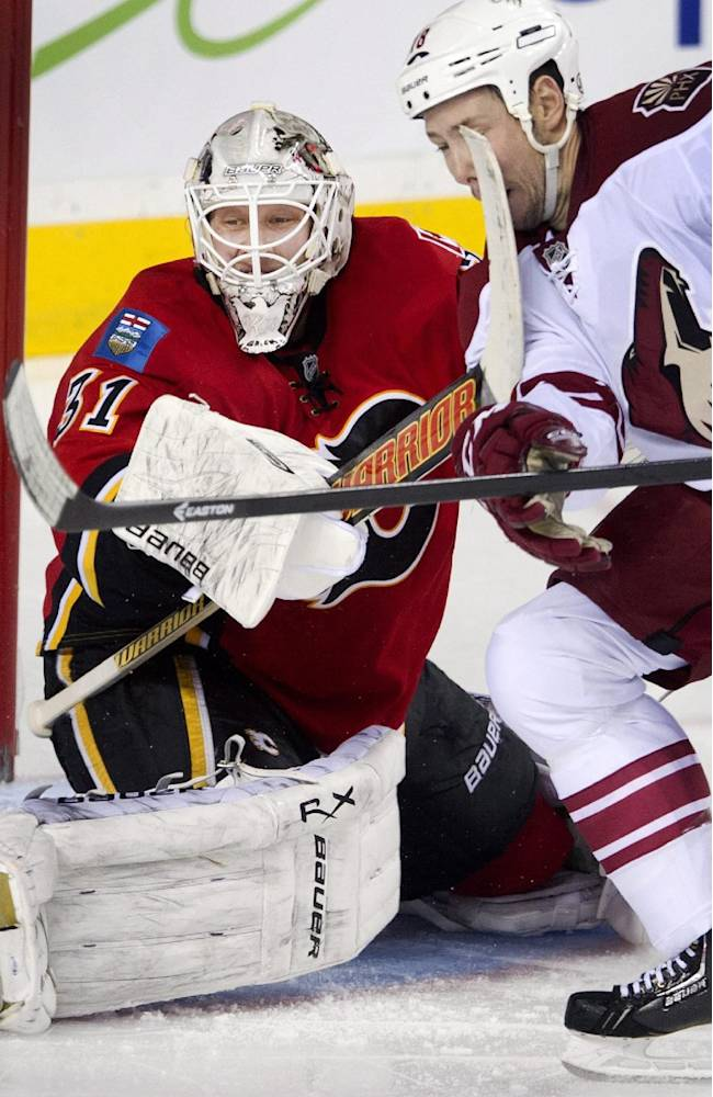Calgary Flames' goalie Karri Ramo, left, from Finland, takes a high sticking penalty on Phoenix Coyotes' David Moss during third period NHL action Wednesday, Dec. 4, 2013 in Calgary, Alberta