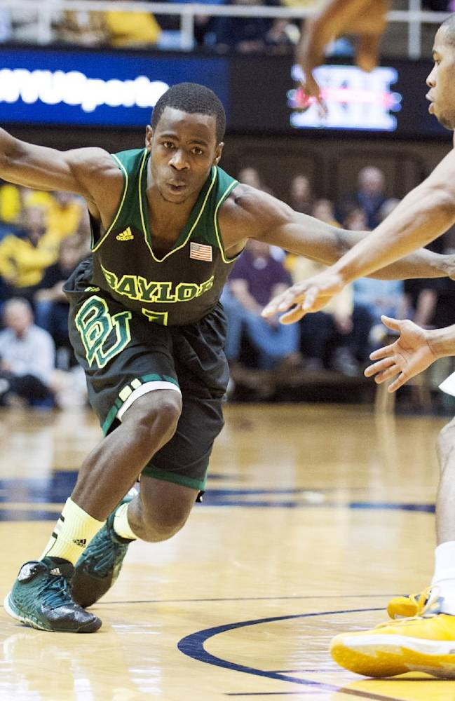 Baylor's Kenny Chery, left, drives by West Virginia's Gary Browne during the second half of an NCAA college basketball game Saturday, Feb. 22, 2014, in Morgantown, W.Va. Baylor won 88-75