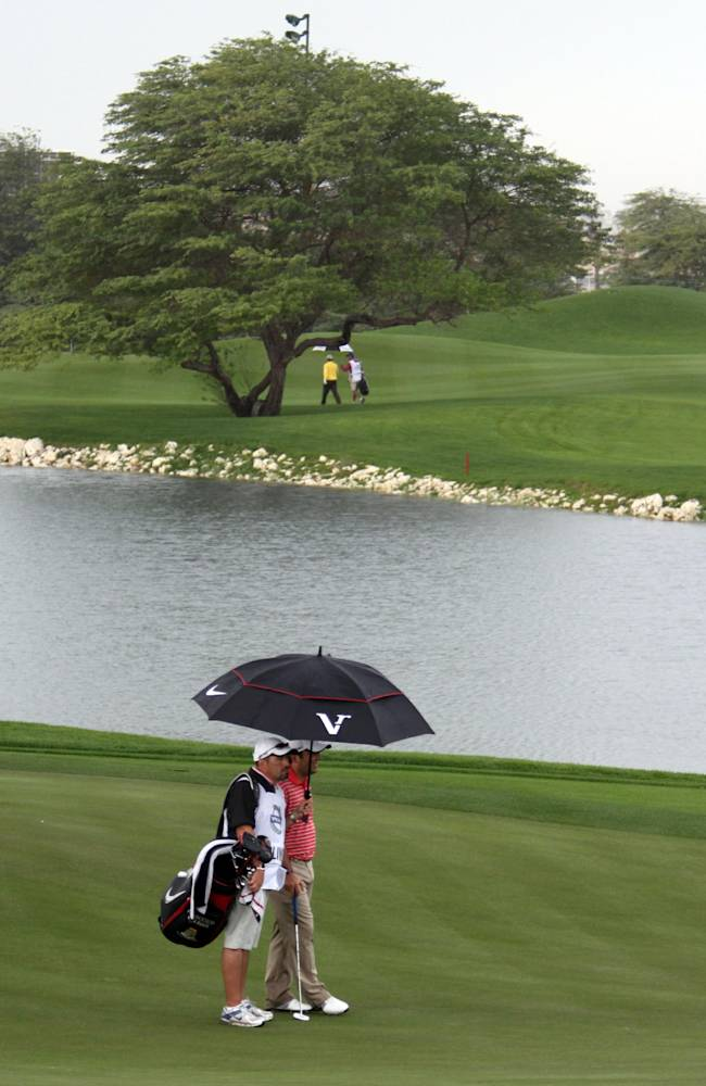 Francesco Molinari, right, of Italy takes cover with his caddie during a brief rain shower Friday, Jan. 28, 2011, at the second round of the European Tour's Volvo Golf Champions Tournament at the Royal Golf Club in Riffa, Bahrain