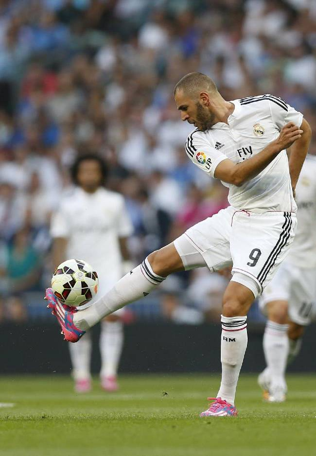 Real Madrid's Karim Benzema, center, duels for the ball with Cordoba's Rossi, left, during a Spanish La Liga soccer match at the Santiago Bernabeu stadium  in Madrid, Spain, Monday, Aug. 25, 2014