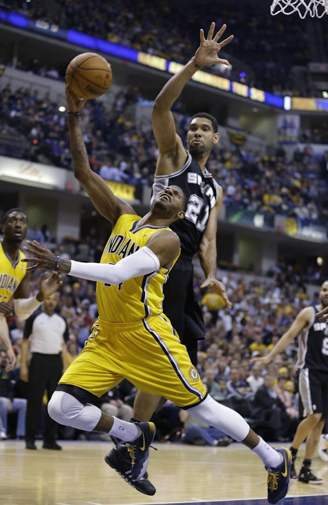 Indiana Pacers forward Paul George, left, is fouled from behind by San Antonio Spurs forward Tim Duncan in the first half of an NBA basketball game in Indianapolis, Monday, March 31, 2014