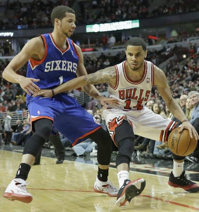 Chicago Bulls guard D.J. Augustin, right, drives against Philadelphia 76ers guard Michael Carter-Williams during the second half of an NBA basketball game in Chicago on Saturday, Jan. 18, 2014. The Bulls won 103-78