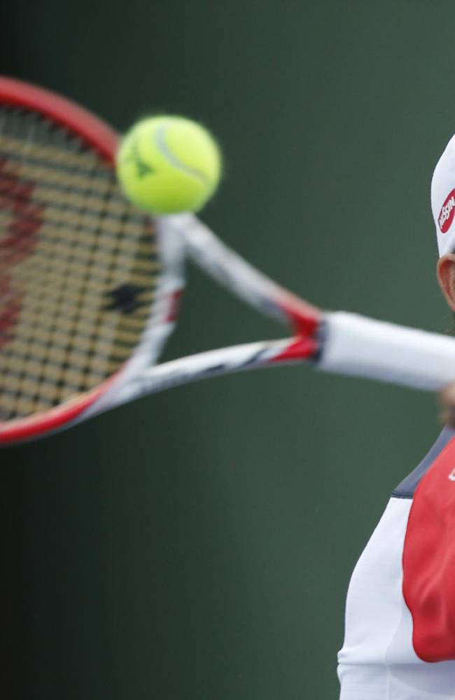 Kei Nishikori of Japan returns a shot to Jo-Wilfried Tsonga of France during the mens singles match of the Shanghai Masters tennis tournament at Qizhong Forest Sports City Tennis Center, in Shanghai, China, Thursday, Oct. 10, 2013
