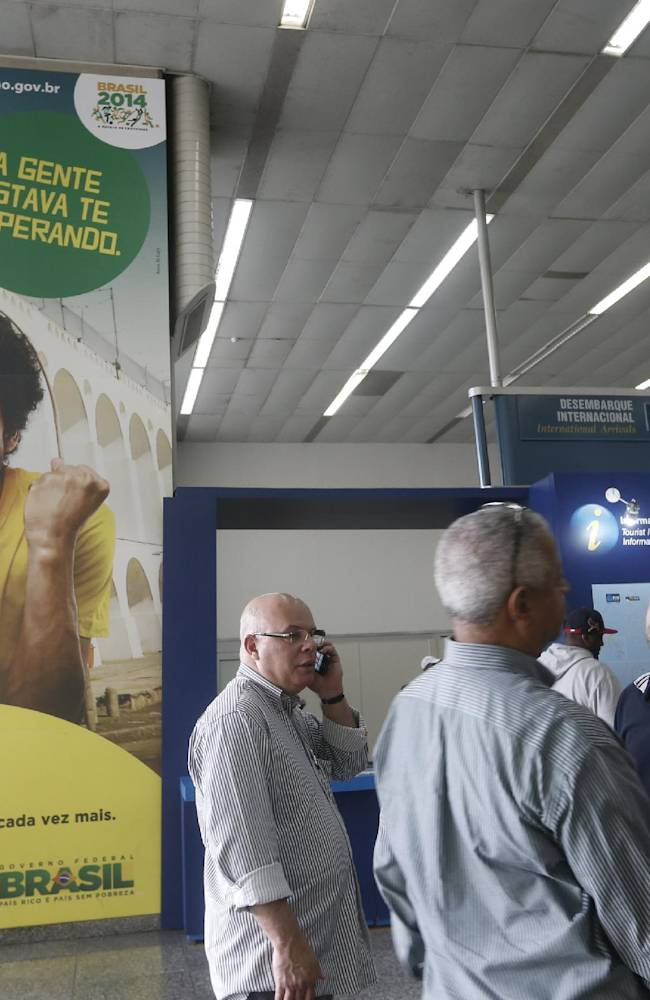 People wait for their flights in front of a banner that reads in Portuguese