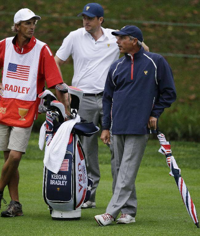 United States team captain Fred Couples, right, waits with Keegan Bradley, middle, and caddie Steve Hale on the 18th fairway during the foursome match at the Presidents Cup golf tournament at Muirfield Village Golf Club Sunday, Oct. 6, 2013, in Dublin, Ohio