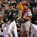 Pittsburgh Pirates' Ike Davis, second from left, celebrates with teammates from left, Andrew McCutchen, Neil Walker, rear, and Pedro Alvarez (24), who were on base for his first home run with the Pirates, a grand slam off Cincinnati Reds starting pitcher