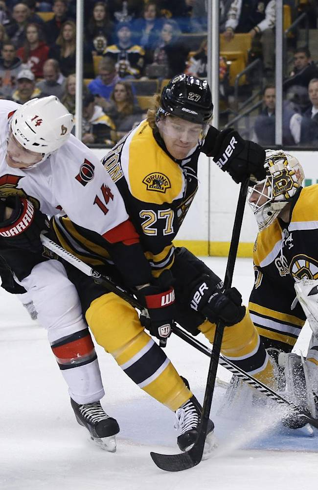 Boston Bruins defenseman Dougie Hamilton (27) keeps Ottawa Senators left wing Colin Greening (14) from getting position as Boston Bruins goalie Chad Johnson (30) protects the net during the first period of an NHL hockey game in Boston, Saturday, Feb. 8, 2014