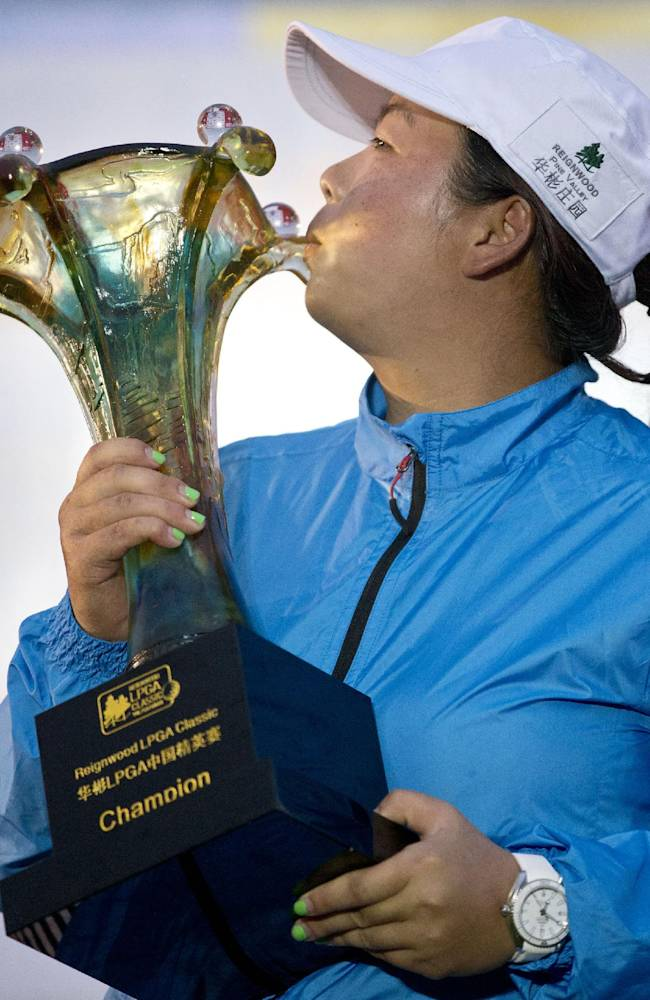 China's Feng Shanshan kisses her trophy after winning the Reignwood LPGA Classic golf tournament at Pine Valley Golf Club on the outskirts of Beijing, China, Sunday, Oct. 6, 2013