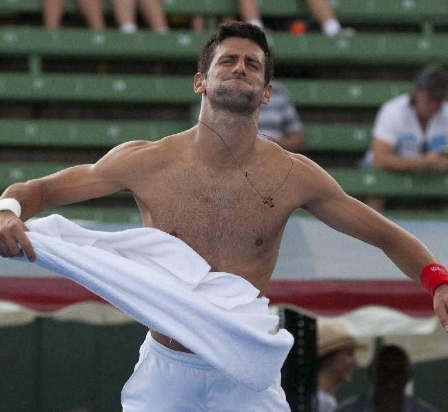 Serbia's Novak Djokovic jokes with the crowd as he takes his shirt off during his match against Juan Monaco of Argentina at the Kooyong Classic ahead of the Australian Open tennis championship in Melbourne Australia, Thursday, Jan. 9, 2014