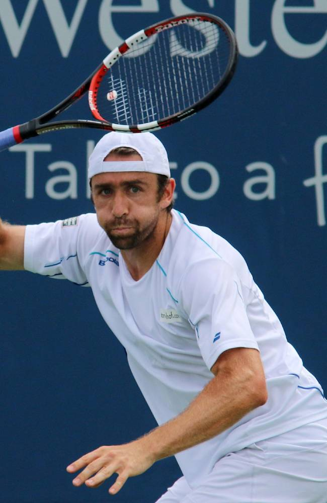 Benjamin Becker, of Germany, returns a volley to Stan Wawrinka, of Sweden, at the Western & Southern Open tennis tournament, Tuesday, Aug. 12, 2014, in Mason, Ohio