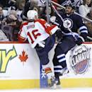 Winnipeg Jets' Dustin Byfuglien, right, and Florida Panthers' Aleksander Barkov (16) collide during the second period of an NHL hockey game in Winnipeg, Manitoba on Friday, Dec. 20, 2013. (AP Photo/The Canadian Press, John Woods)