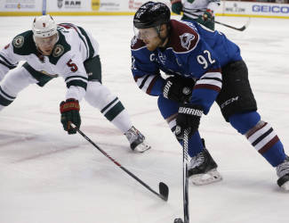 Minnesota Wild defenseman Christian Folin, left, defends against Colorado Avalanche left wing Gabriel Landeskog, both of Sweden, as he works the puck in for a shot in the first period of an NHL hockey game Saturday, Feb. 28, 2015, in Denver. (AP Photo/David Zalubowski)