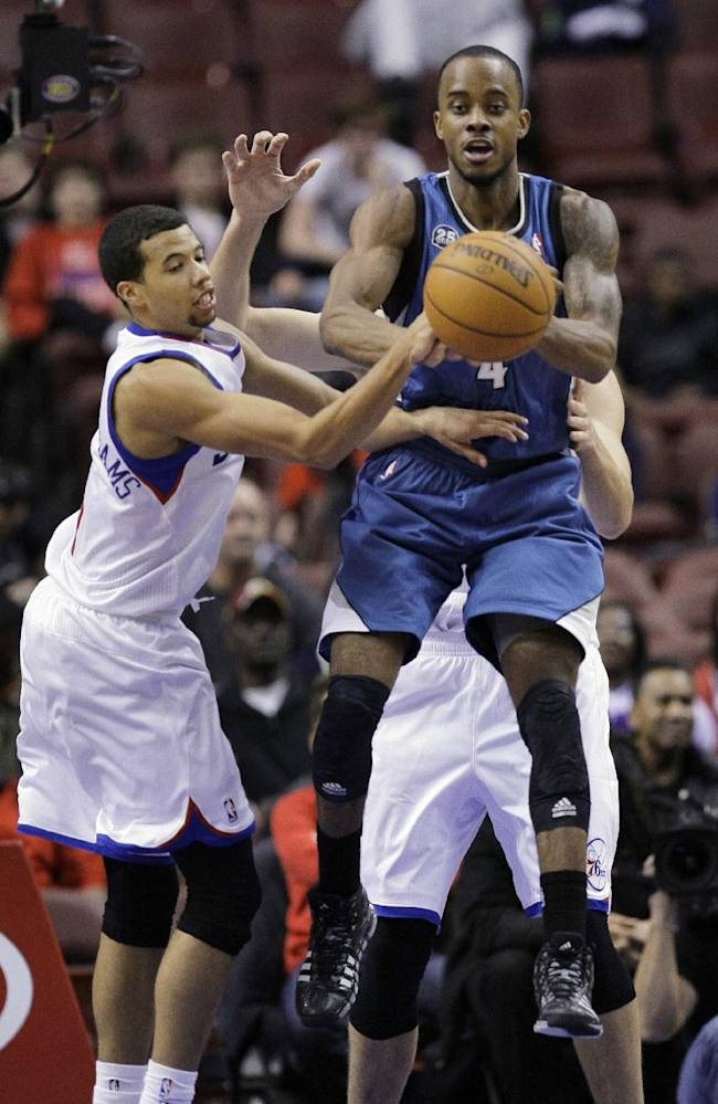 Minnesota Timberwolves' Lorenzo Brown, right, grabs a rebound away from Philadelphia 76ers' Michael Carter-Williams in the second half of a preseason NBA basketball game Wednesday, Oct. 23, 2013, in Philadelphia. Timberwolves won 125-102