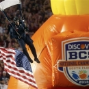 FILE - In this Jan. 7, 2013, file photo, a member of the U.S. Army jumps into the stadium before the first half of the BCS National Championship college football game between Alabama and Notre Dame in Miami. The conference commissioners in charge of putting together the four-team playoff system that will start after the 2014 regular season will meet starting Tuesday, April 23, 2013, in Pasadena, Calif. At the top of their agenda: Pick three more bowls to be used in the semifinal rotation and decide on a site for the first national championship game. (AP Photo/John Bazemore, File)