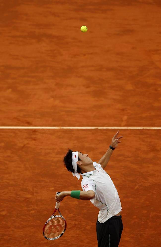 Kei Nishikori from Japan serves the ball during a Madrid Open tennis tournament match against David Ferrer in Madrid, Spain, Saturday, May 10, 2014