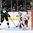 Calgary Flames goalie Joni Ortio makes a save as Los Angeles Kings center Jeff Carter attempts a shot on a Kings power play during the second period of an NHL hockey game, Monday, Jan. 19, 2015, in Los Angeles The Associated Press