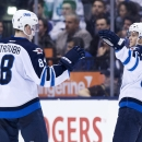 Winnipeg Jets defenseman Tobias Enstrom, right, celebrates his goal with teammate Jacob Trouba, left, while playing against the Toronto Maple Leafs during second-period NHL hockey game action in Toronto, Saturday, April 5, 2014 The Associated Press