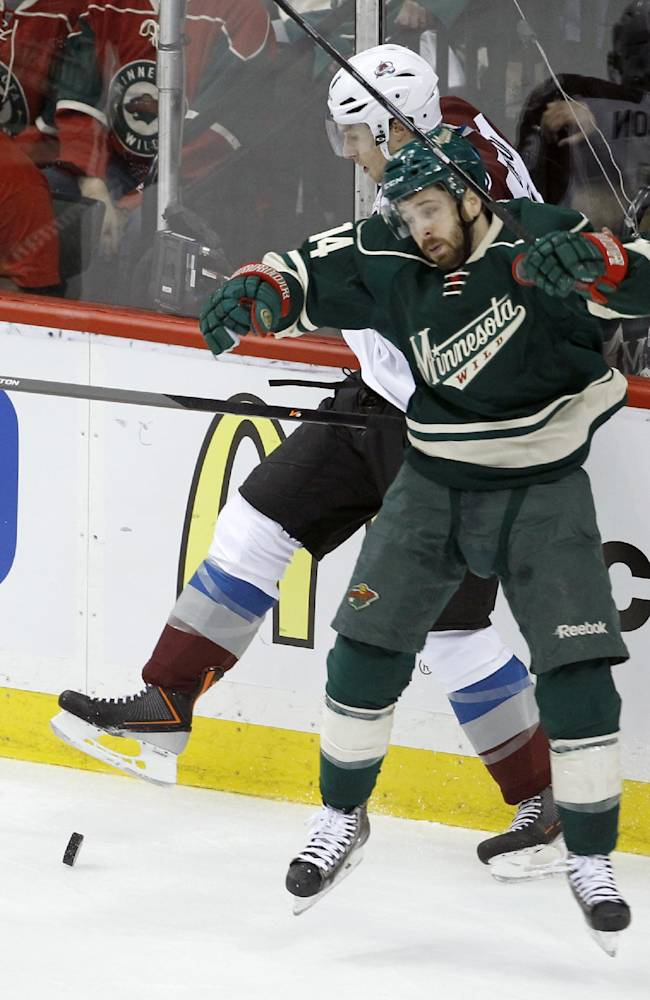 Minnesota Wild right wing Justin Fontaine (14) checks Colorado Avalanche defenseman Erik Johnson, rear, off the puck during the first period of Game 3 of an NHL hockey first-round playoff series in St. Paul, Minn., Monday, April 21, 2014