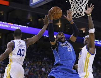 Dallas Mavericks' Vince Carter (25) shoots between Golden State Warriors' Harrison Barnes, left, and Jermaine O'Neal during the first half of an NBA basketball game, Tuesday, March 11, 2014, in Oakland, Calif. (AP Photo/Ben Margot)