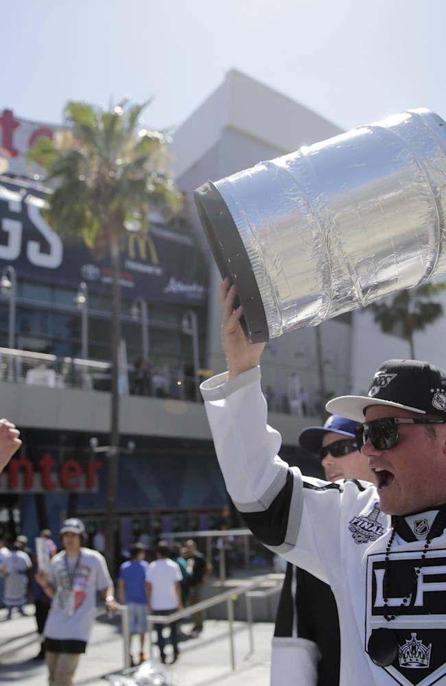 Los Angeles Kings fan Tim Bressler, right, of Newport Beach, Calif., carries a trophy in front of the Staples Center before the Kings face the New York Rangers in Game 5 of the Stanley Cup Final series Friday, June 13, 2014, in Los Angeles